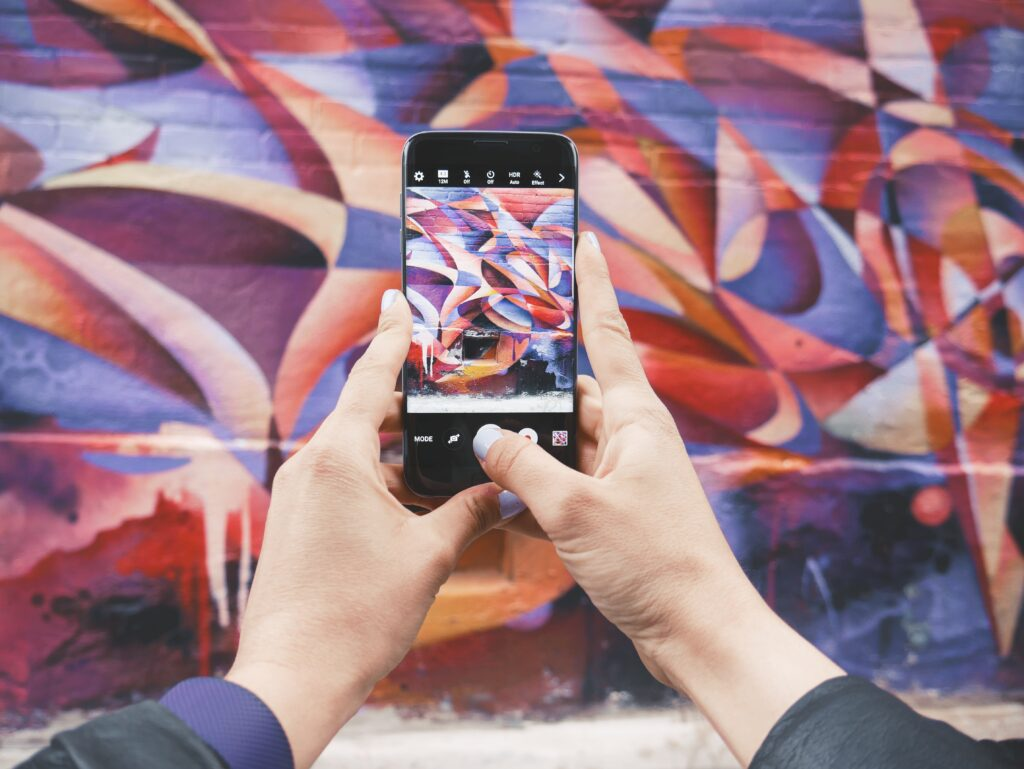 person taking user-generated content photo of wall on phone