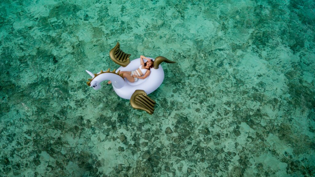 aerial picture woman in unicorn floaty