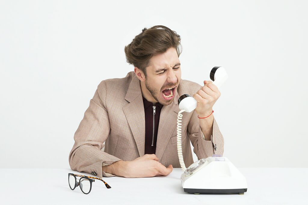 man in jacket yelling into phone