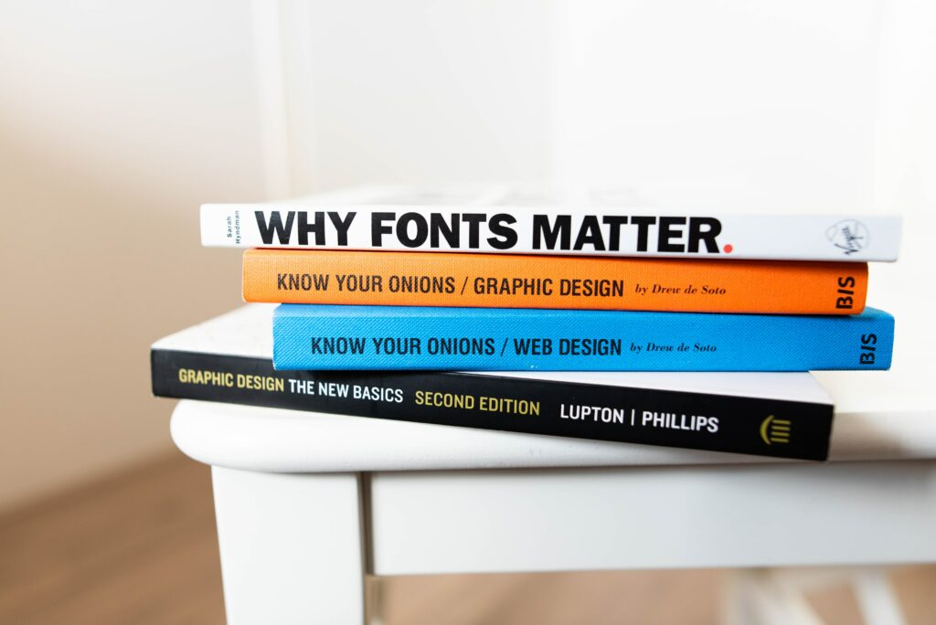 graphic design educational books stacked on table